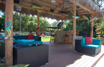 tiki hut with outdoor furniture in a landscaped garden