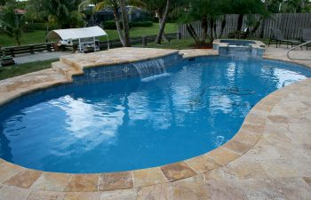 backyard swimming pool with waterfall and artistic pavers patio after renovation