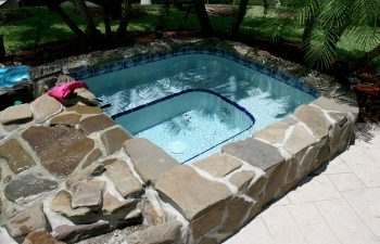 backyard in-ground jacuzzin with natural stone finishing