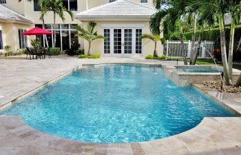 backyard swimming pool with jacuzzi and paver patio after renovation