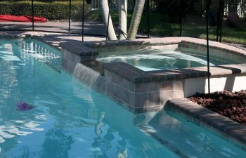 fenced backyard swimming pool with brick paver patio before renovation