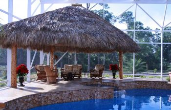 garden indoor swimming pool with a tiki hut and comfortable seats on a pool patio