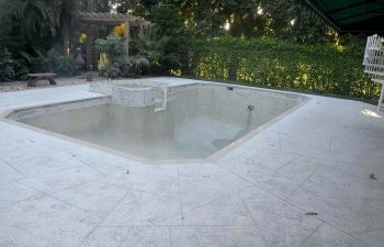 backyard swimming pool with jacuzzi and pool deck under renovation