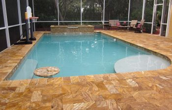glass enclosed swimming pool with Travertine deck after renovation