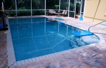glass enclosed swimming pool and deck before renovation