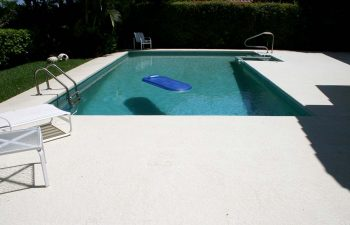 backyard in-ground swimming pool with jacuzzi and paver deck after renovation