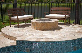 backyard swimming pool patio with a fire pit and seats around it