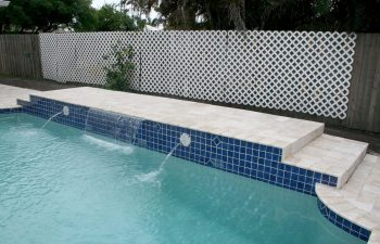 backyard swimming pool with decorative tiles and waterfalls