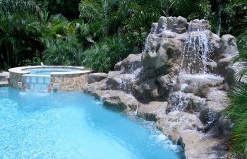 outdoor spa pools with a hardscape waterfall on the pool edge