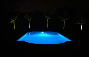 night view of a backyard swimming pool