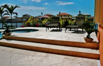 artistic pavers patio with sunbeds by a backyard swimming pool