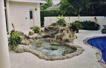 hardscape waterfall on a backyard pool deck