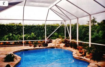 glass enclosed swimming pool with hardscape waterfall and plants on the pool deck