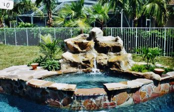 backyard spa pool with a hardscape waterfall