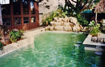 backyard swimming pool with green water color and a hardscape waterfall