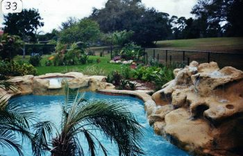 backyard spa pools with a hardscape waterfall