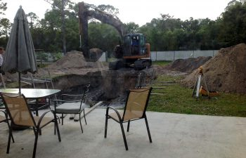 backyard swimming pool under construction - digging excavation with JCB machinery