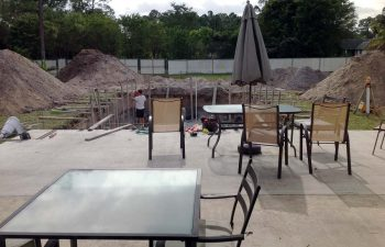 backyard swimming pool under construction - a specialist working in the excavation