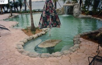 backyard swimming pool with a hardscape waterfall and flagstone patio