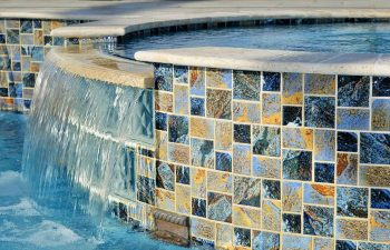 backyard swimming pool with waterfalls coming down walls with decorative tiles