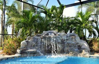 garden indoor swimming pool with a hardscape waterfall and palms by the pool edge
