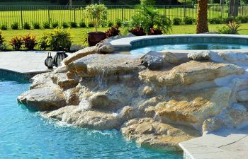 backyard spa pools with a hardscape waterfall formed between jacuzzi and pool
