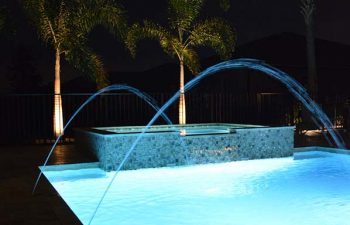 night view of a bakyard swimming pool with fountains