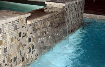 backyard spa pool with a waterfall and decorative tiles