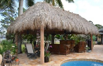 tiki hut with garden furniture by an outdoor spa pool