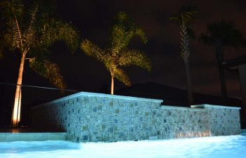night view of a bakyard spa pool with waterfall