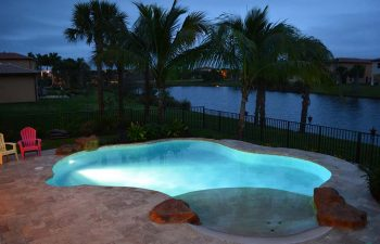 night view of a backyard beach entry swimming pool