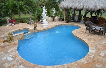 backyard swimming pool with Travertine deck and outdoor furniture under tiki roof and