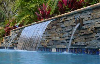 backyard pool waterfall coming out a stone brick wall