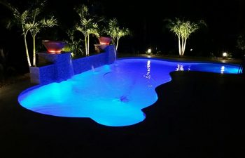 night view of a backyard swimming pool and outdoor lighting