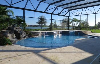 glass enclosed swimming pool with waterfall and hardscapes