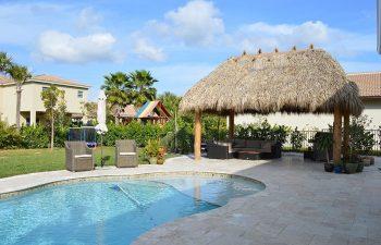 Tiki hut and outdoor furniture on a backyard pool deck