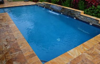backyard swimming pool with waterfall and Travertine deck
