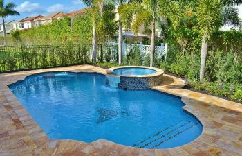 a backyard swimming pool with jacuzzi and Travertine deck