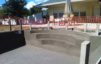 backyard swimming pool under construction - shaped entry steps