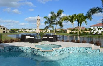 backyard swimming pool with light blue water color and jacuzzi