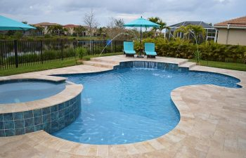backyard swimming pool with water features and sunbeds on a deck
