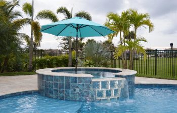 blue sun umbrella over a jacuzzi and backyard swimming pool