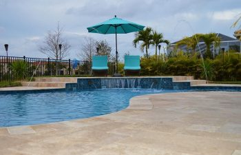 backyard swimming pool with waterfall Travertine paver patio