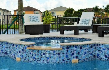 sunbeds on a pool patio with built-in jacuzzi