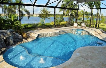 glass enclosed swimming pool with jacuzzi and waterfalls