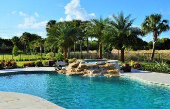 backyard swimming pool with a waterfall