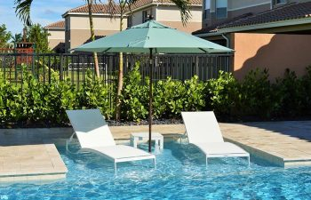 two sunbeds under umbrella placed in a swimming pool basin