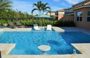 backyard swimming pool with sunbeds and sun umbrella