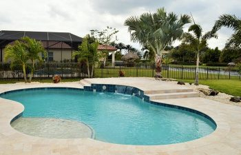 backyard swimming pool with water features and Travertine deck
