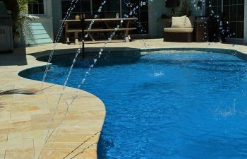 backyard swimming pool with fountains and Travertine deck